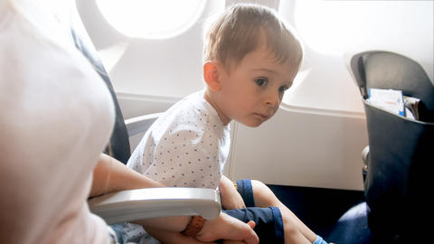 Portrait of little toddler boy feeling nervous before first flight in airplane Photo