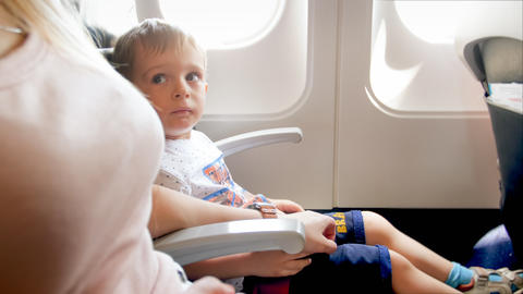 Cute toddler boy sitting on passenger seat in airplane and looking at mother フォト