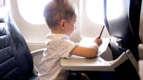 Toned image of cute toddler boy drawing in copybook during flight in airplane Photo