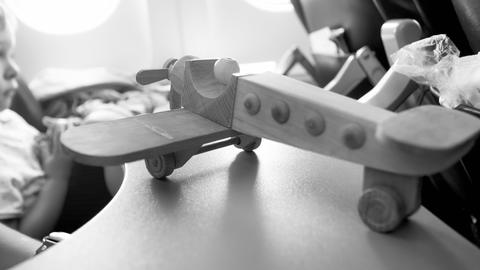 Closeup black and white image of wooden miniature airplane against illuminator Photo
