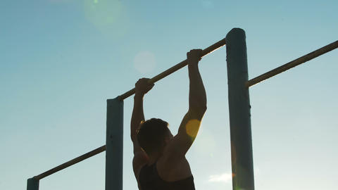 Male athlete training on chin-up bars outdoors, physical strength and sport Live Action