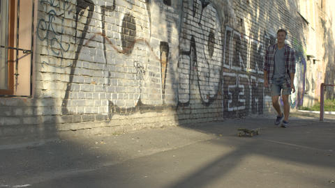 Vigorous young person riding skateboard near graffiti… Stock Video Footage
