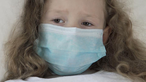 Seriously ill female kid in medical mask looking at syringe with scared eyes Live Action