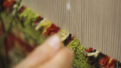 Woman weaving traditional handmade carpet of wool using special equipment Live Action