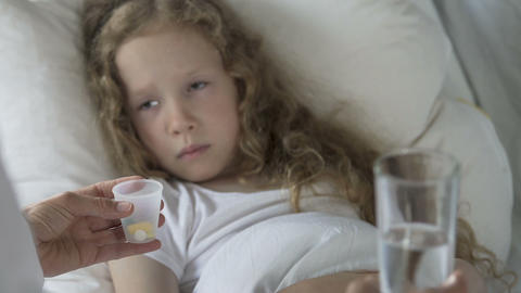 Sad Caucasian child lying in bed and looking at pills in doctor's hands, illness Footage
