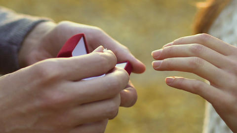 Man putting silver engagement ring on woman hand, proposal in the autumn park Live Action