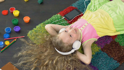 Young smiling girl singing favourite song in big white headphones, enjoyment Live Action