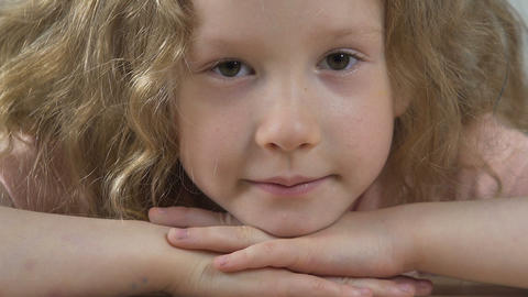 Beautiful little girl motionlessly staring into camera, deep and soulful look Footage