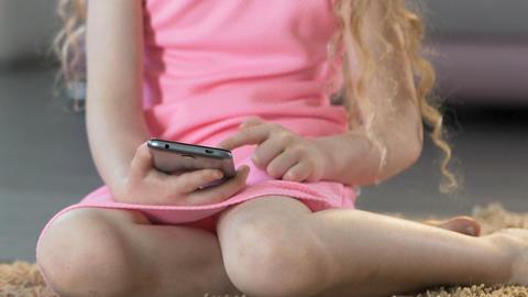 Little long-haired girl scrolling on smartphone, surfing…, ライブ動画