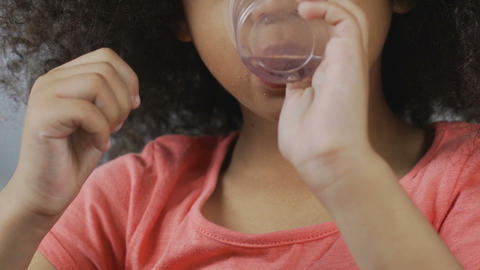 Little african-american girl drinking clear water from plastic glass, beverage Live Action