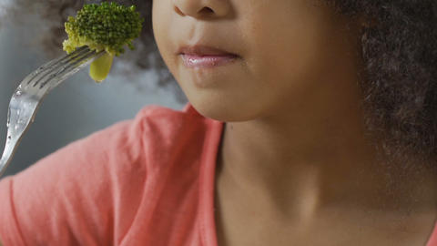 Young girl tries broccoli and hates it, children can't stand raw vegetables Footage