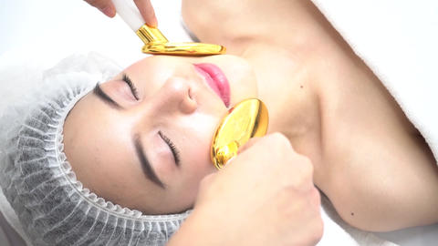 Asian Woman getting golden spoon medical beauty device on face at beauty clinic Footage