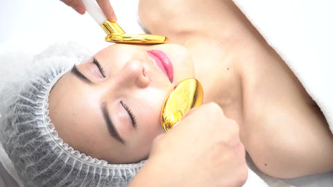 Asian Woman getting golden spoon medical beauty device on… Stock Video Footage