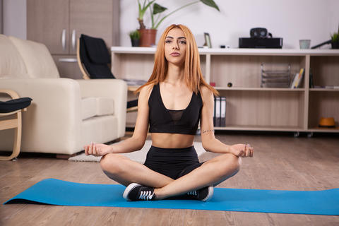 Attractive young girl sitting in lotus yoga position in her house Photo