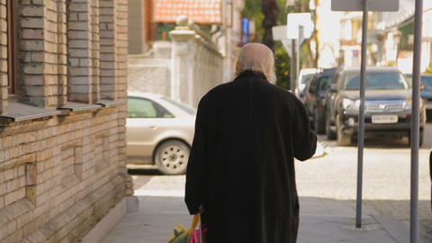 Elderly man walking in city street, retirement problems, loneliness in old age Live Action