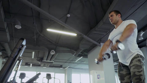 Handsome guy doing exercises with dumbbells in the gym Live Action