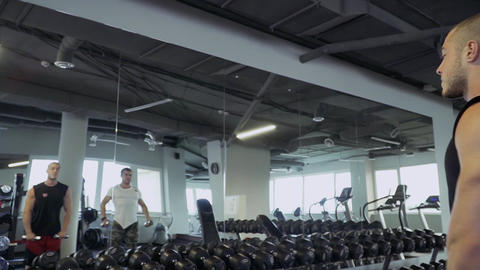 Two strong guys doing exercises in the gym Live Action