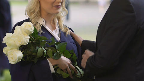 Caring father congratulating beloved daughter on graduation, presenting bouquet Live Action