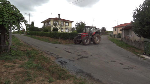 Farm tractor coming from the street and turns to the left, on another street, be Live Action
