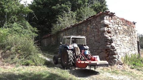 Farm tractor small that climb along a high stone wall next to a forest 54 Footage