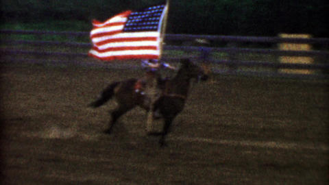 1955: USA flag proudly flown by a horse riding cowboy for rodeo Footage
