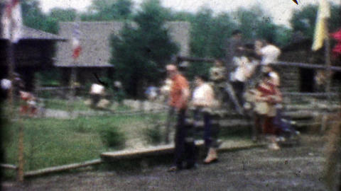 1955: Horse riding cowboys carry flags while folks watch the rodeo Footage