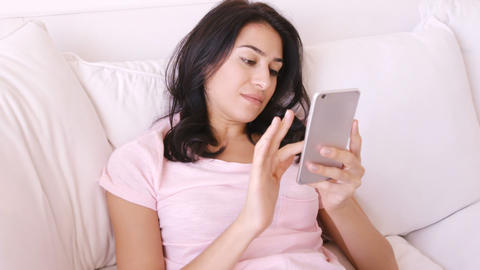 Woman sitting on a sofa using her smartphone Live Action