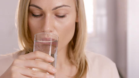 Close up on a woman drinking a glass of water Live Action