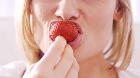 Close up on a blonde woman eating a strawberry Live Action
