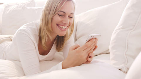 Blonde woman lying on a sofa using her smartphone and smiling Live Action
