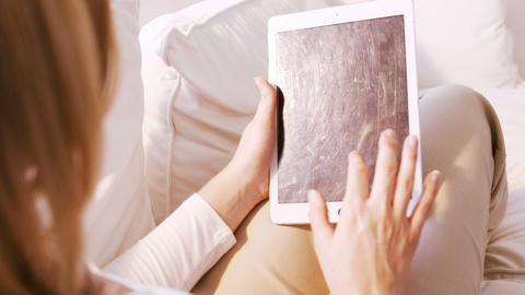Woman front the back using tablet on a sofa Stock Video Footage