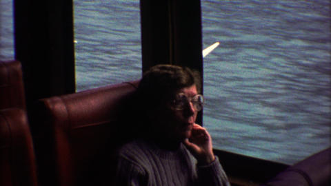 1974: Lonely women on train looks out window cracks smile and waves Footage