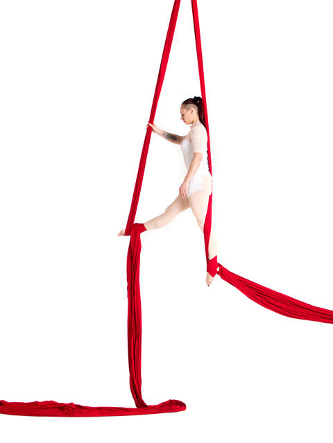 Woman hanging in aerial silks, isolated on white フォト