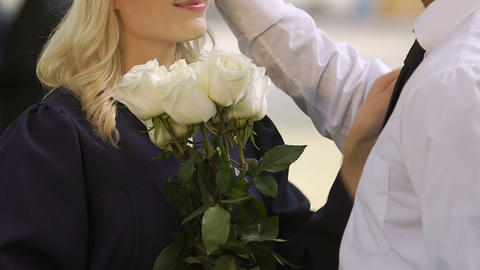 Man congratulating girlfriend on university graduation ceremony with flowers Live Action