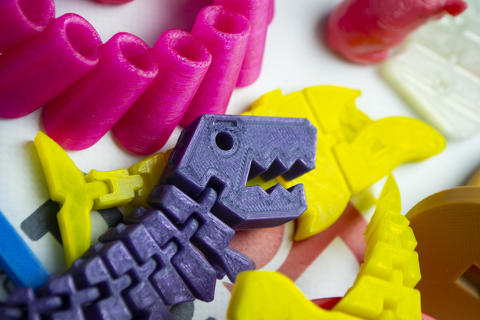 Many bright multi-colored objects printed on 3d printer lie on flat surface Photo
