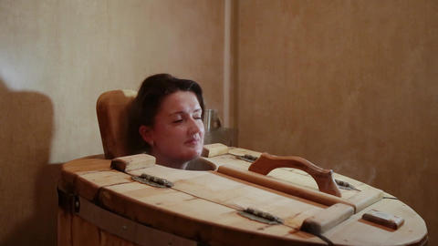 Female head sticking out of the cedar barrels at a spa salon. Blonde woman Footage