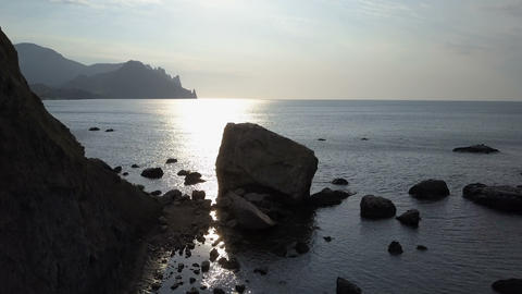 Flight over the sea, rocks and stones at sunrise. Mountains, rocks, stones in Live Action