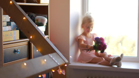 The young ballerina sits on the window and holds flowers in her hands Footage