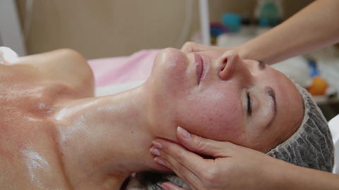 Very beautiful girl doing facial massage at the spa salon. Healthy lifestyle Live Action