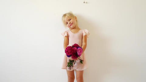 Young dancer posing with a bouquet of flowers. Happy little ballerina Footage