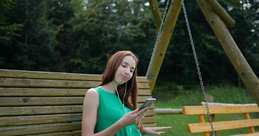 Young girl listeting music on the swing Footage