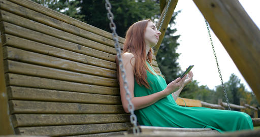 Young girl listeting music on the wooden swing GIF