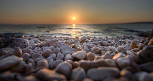 Beach pebbles at sunset, close up macro フォト