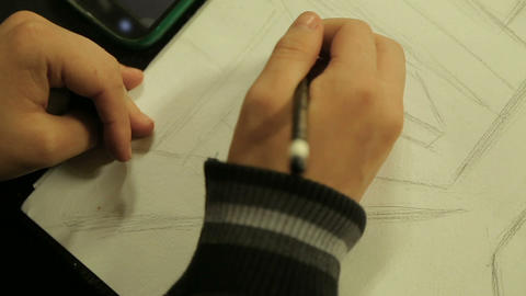 Young artist making a sketch with pencil, copying image from cellphone, hobby Live Action