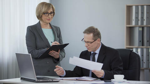 Satisfied male boss happy with correct report by woman accountant, good done job Live Action