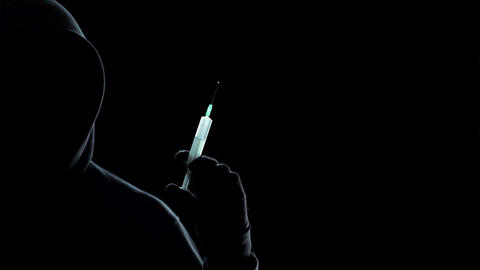 Silhouette of faceless man in hoodie holding syringe with toxic acid, crime Footage