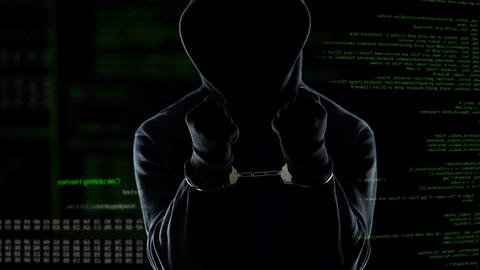 Male hacker with handcuffs standing in front of animated computer code, IT thief Live Action