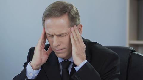 Businessman suffers from sick headache, problem at work, stress from overworking Live Action