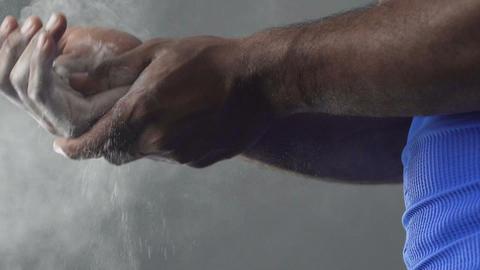 Sportsman putting talcum powder on hands, athlete preparing before contest Live Action