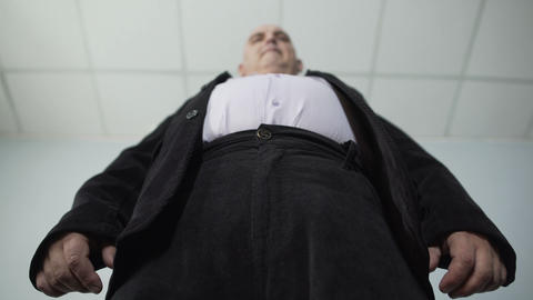 Overweight male trying to fasten a button on his jacket, bottom view of fat man Footage